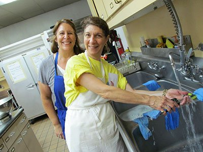 Even dishes are fun for Barbara and Mary, kitchen volunteers.