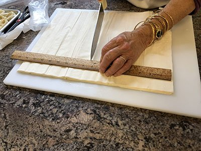 It takes great precision to measure and cut the phyllo dough.  Thank goodness for a ruler and a sharp knife!