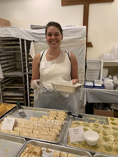 Emily, food festival volunteer coordinator (and part of the virtual festival committee!), helps a visitor decide which types of baklawa to take home in a box.