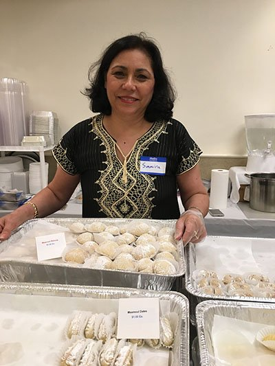 Festival Sweets Chair Samira proudly holds a tray of maamoul as the festival gets started.  She is extremely grateful for the support of her fellow parishioners who worked diligently over the prior weeks to hand make thousands of sweets for sale over the Labor Day weekend event.