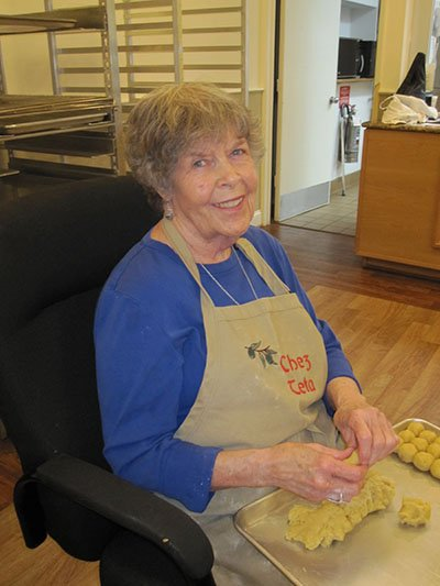 """Teta"" is grandmother in Arabic, and here, sporting her ""Chez Teta"" apron, is Mary, mother to 9, grandmother to 28, and longtime leader of the date maamoul cookie baking at Holy Transfiguration Church."